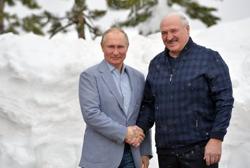 Russian President Vladimir Putin (L) shakes hands with Belarus President Alexander Lukashenko against a snowy background in the Black sea resort of Sochi, Russia, February 2021.