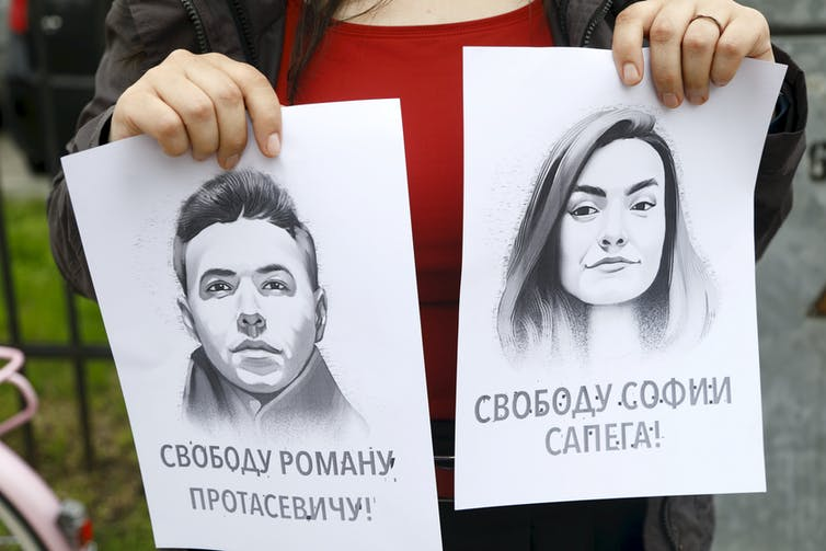 A woman holds portraits of journalist Roman Protasevich and his girlfriend Sofia Sapega.