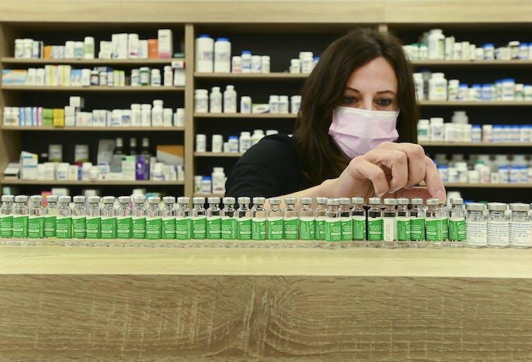 A woman lining up vials on a shelf