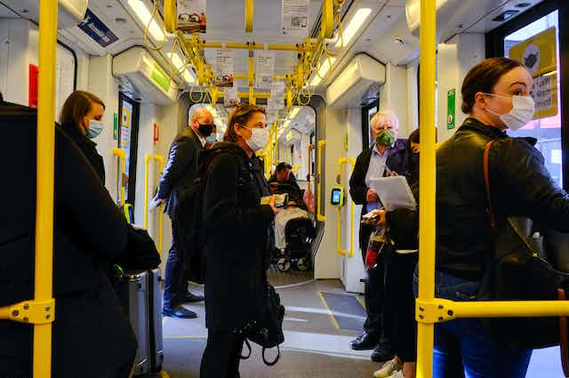 People in masks travel on a tram.