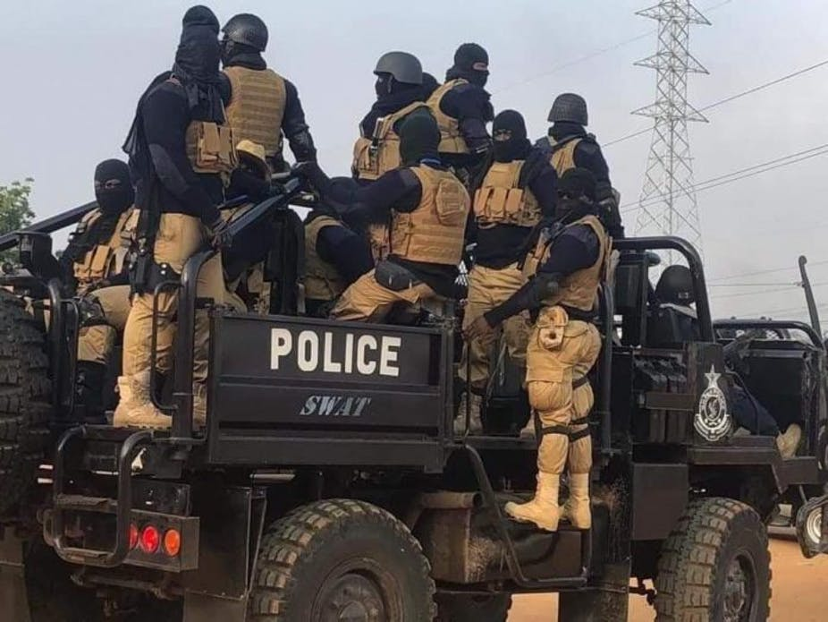 Masked, armed men in an armoured police vehicle