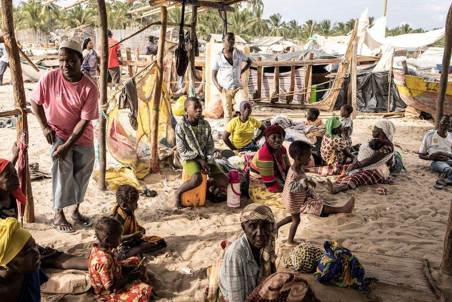 Men, women and children sit on beach sand in a makeshift shelter.