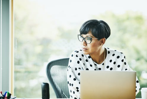 woman at laptop pensively looks off into distance