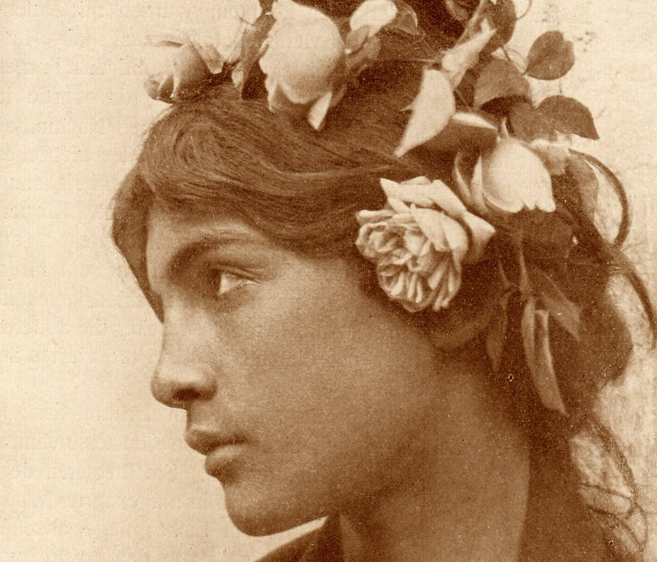 A boy wears a wig with flowers affixed to it.