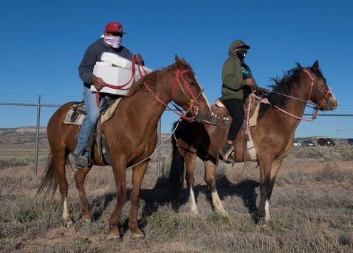 Native Americans of the Navajo Nation people, pick up supplies on horses at a food bank.