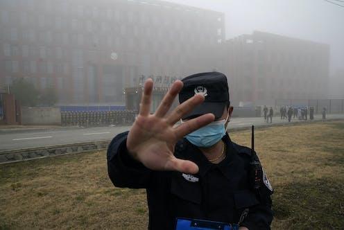 Gardien de sécurité lève la main pour empêcher des gens d'entrer dans le périmètre de sécurité de l'Institut de virologie de Wuhan (WIV