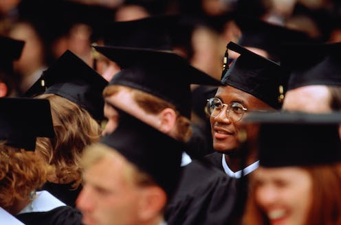 A Black student sits at his college graduation among his classmates.