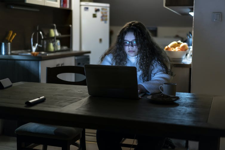 A young girl is working on her laptop late at night.