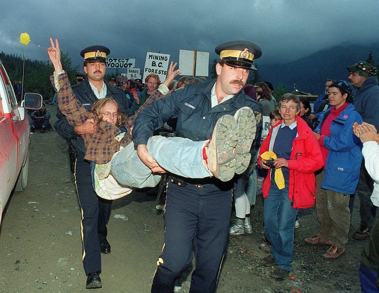 Two police carry a man by his legs and under his arms as a crowd looks on.