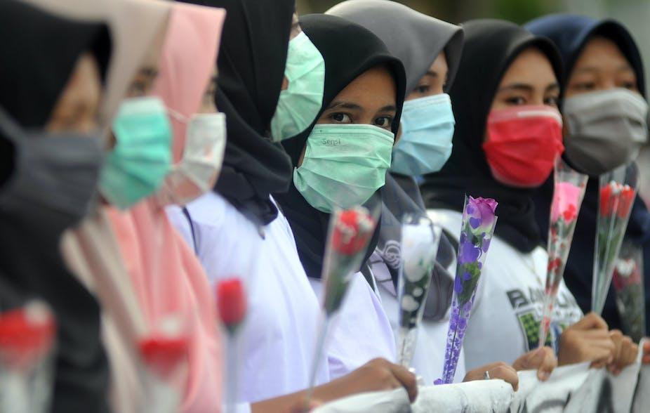 Mahasiswi memegang bunga mawar dan menggunakan masker sambil memperlihatkan spanduk kampanye Anti Kekerasan Seksual Terhadap Perempuan