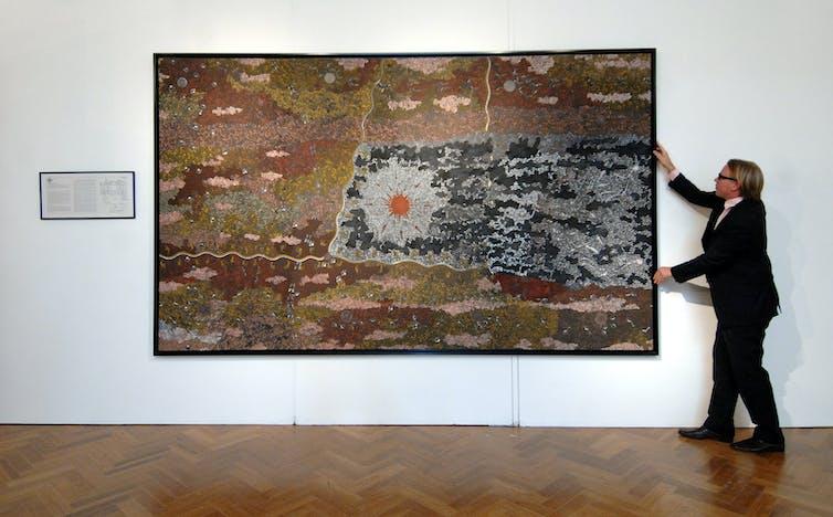 Man hangs large Indigenous painting