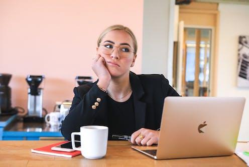 Jeune femme devant un ordinateur, l'air ennuyé