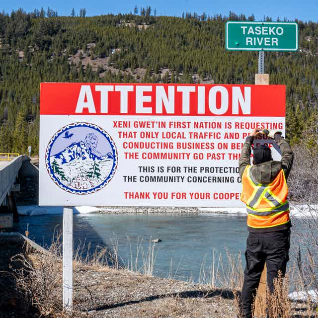 Man stands next to sign that reads 'Attention: Xeni Gwet'in First Nation is requesting that only local traffic and persons conducting business on behalf of the community go past this point'