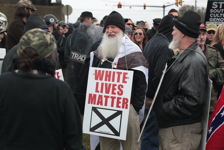 Bearded older man at a white supremacist rally carrying a sign that says 'White Lives Matter'