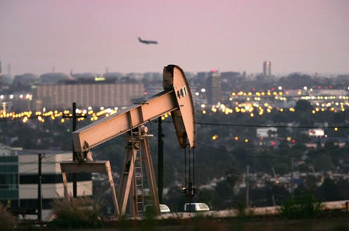 Oil well on a hill near an airport and office buildings, with a plane landing.