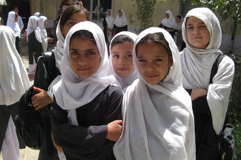 A row of five school girls wearing white hijabs.