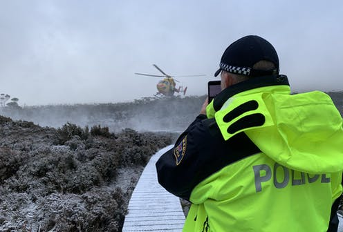 Police officer looks at a helicopter on a wintery trail