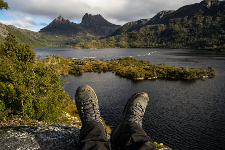Hiking boots overlooking a lake in Cradle Mountain