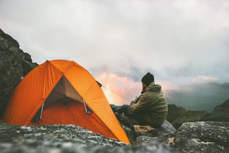 Hiker beside an orange tent