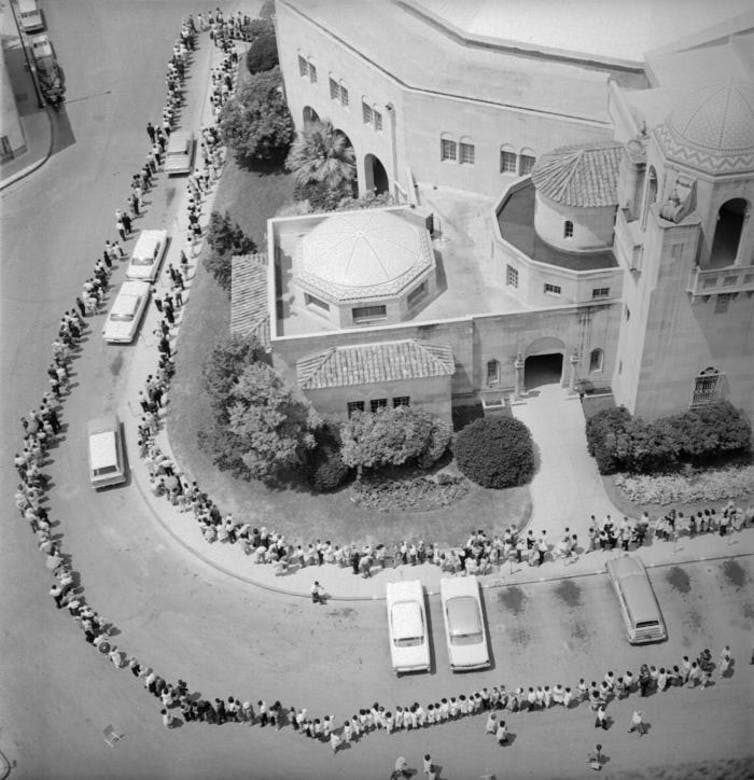 This historic 1962 image depicted an aerial view of a long line of people awaiting their polio vaccination. The line was so long, it surrounded a city auditorium in San Antonio, Texas.
