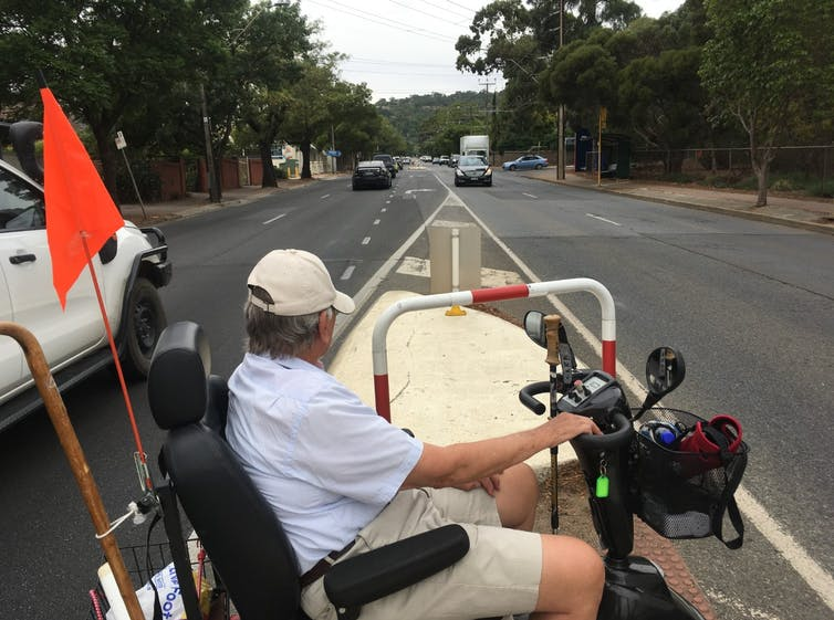 Man on mobility scooter waits in the middle of the road for traffic to pass so he can cross