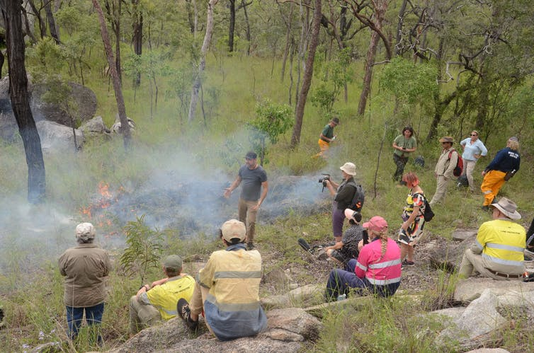 A few people surround a small fire