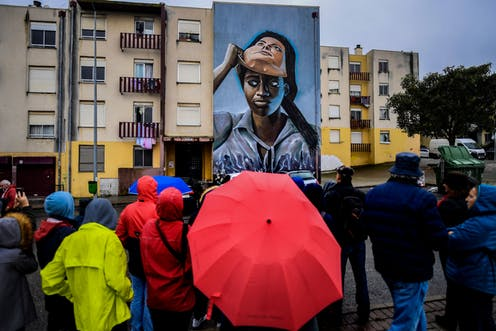 A crowd of people in rainy weather stand and look at a mural that covers a wall of a building. It depicts a dark-skinned woman lifting a white-skinned mask off her face.