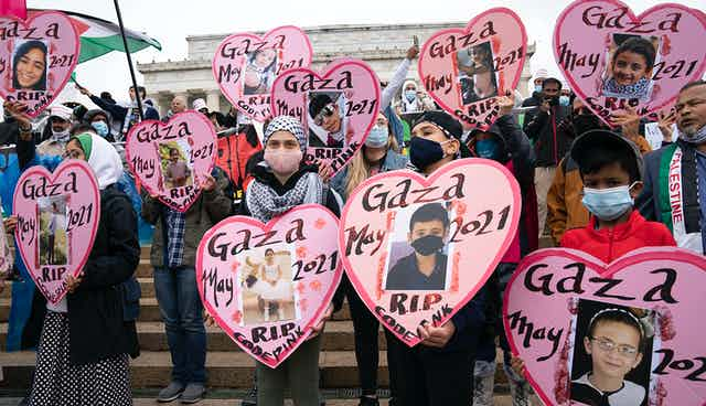 Children demonstrators wearing face masks hold heart shaped pictures of children killed that say Gaza May RIP.