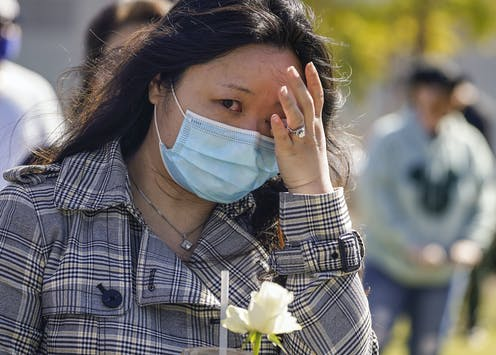 Une femmes asiatique, portant un masque, pleure durant une manifestation