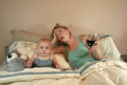 Mom lays in bed with baby. Mom has glass of wine in hand, looks exhausted