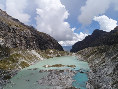 Aerial view of glacial lake with rocky slope, looking into a valley
