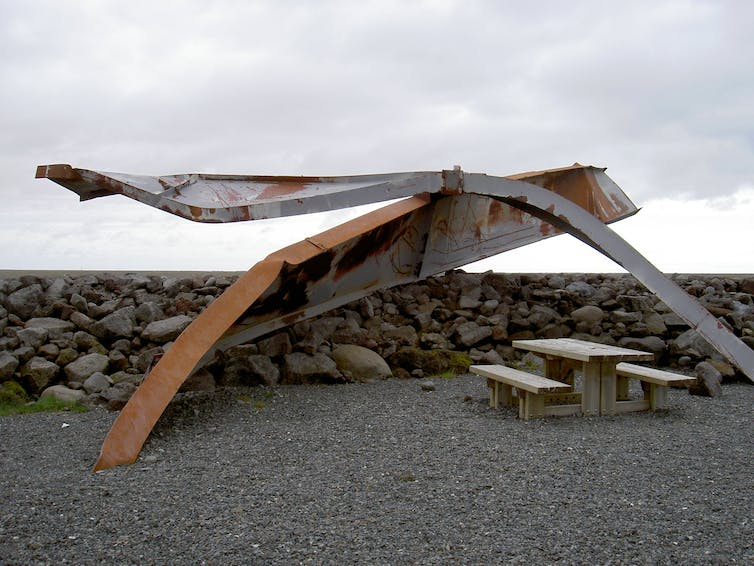 Twisted steel beams near a picnic table.