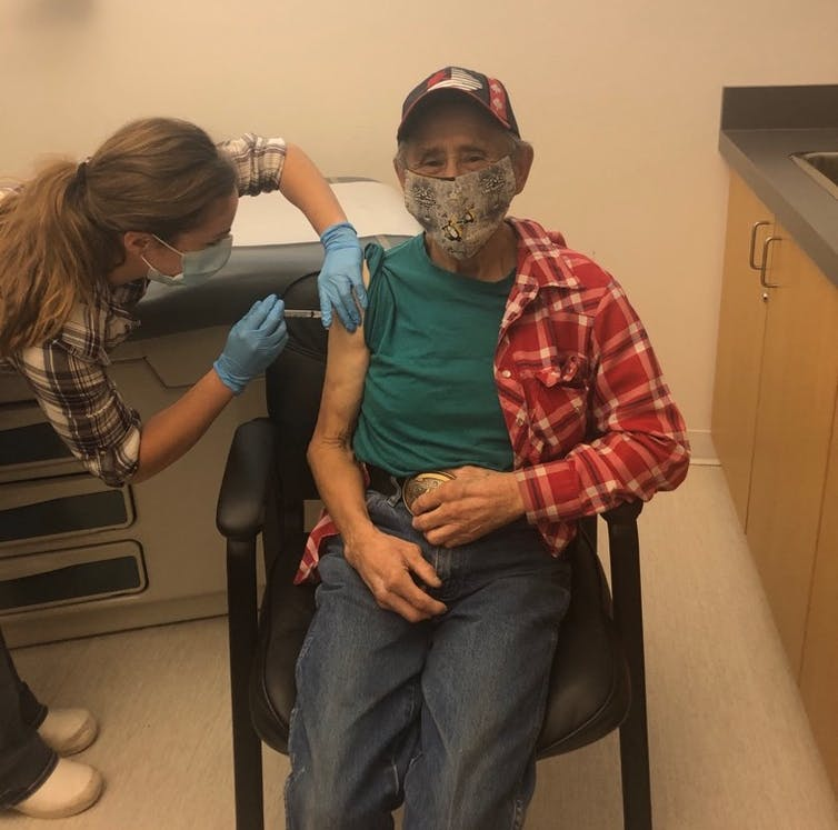 An Indigenous man gets a vaccinne in his right arm