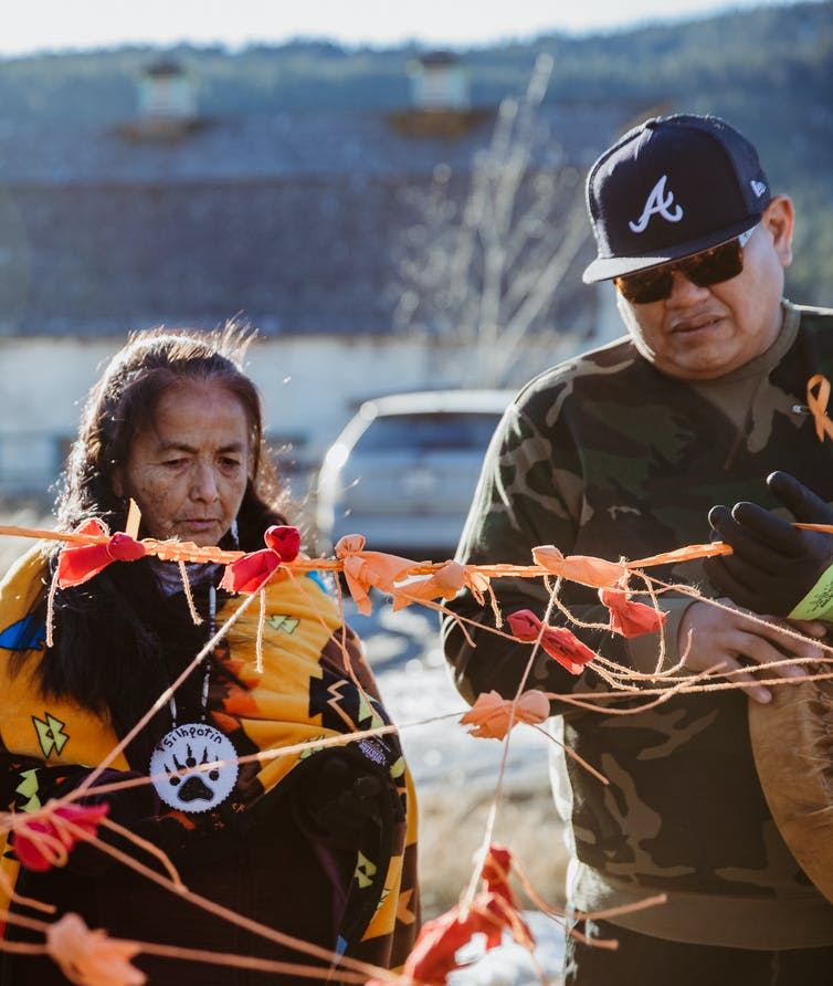 Two Indigenous people (one male, one female) stand around orange ribbon and orange ties.