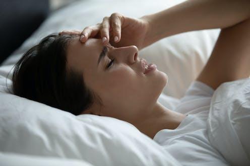 Woman lying in bed headache
