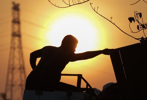 A silhouette of a man loading goods onto a truck at sunset.