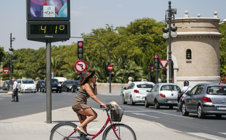 A woman passes traffic on a bike with a digital sign displaying 41℃.