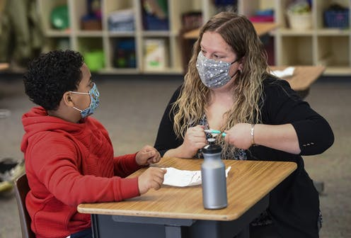 Teacher works with fourth-grade student at school desk