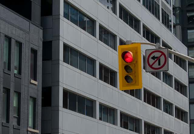 A traffic light with a no left turn sign in a city.