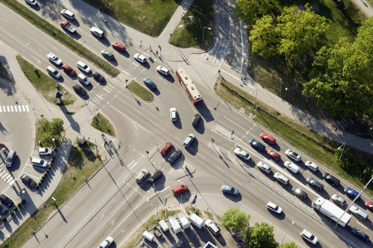 An aerial view of an intersection with cars making a left turn.