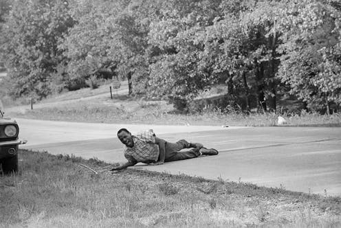 James Meredith, shouting with pain as he pulling himself across the street after being shot