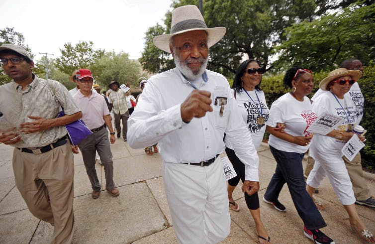 James Meredith, dressed in all white and wearing a straw hat, walks surrounded by others in a 50th anniversary march commemorating his earlier march for voting rights.
