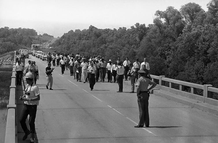 A group of marchers on a highway in northern Mississippi, including civil rights leaders Martin Luther King Jr., Stokely Carmichael and Floyd McKissick.