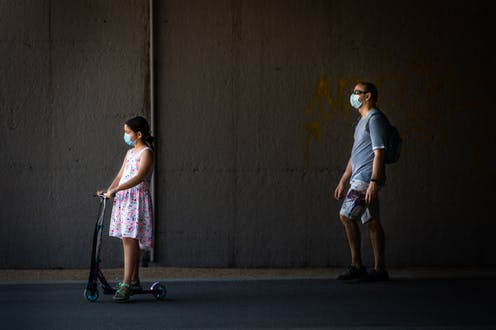 Masked father walks behind masked daughter riding scooter