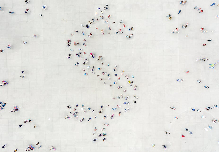 People arranged into the shape of a dollar sign