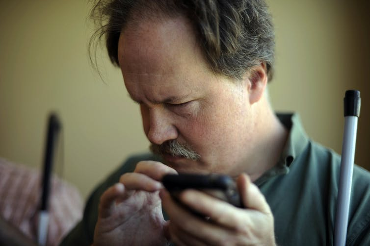 A man holds a smartphone, his face turned away from the screen, a white cane resting against his shoulder