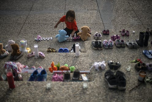 Kid puts candles in shoes surrounded by teddy bears