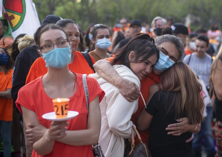 Une femme tient une bougie sur laquelle on peut lire le chiffre 215. Une foule de personnes en deuil portant de l'orange se tient derrière elle