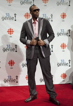 Kardinal Offishall, in a suit and pink shirt, poses on the red carpet.