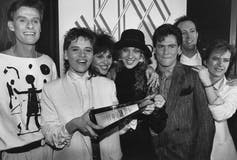 A black and white photo of people in the 1980s including a woman in a white suit and short hair holding a Juno statue.